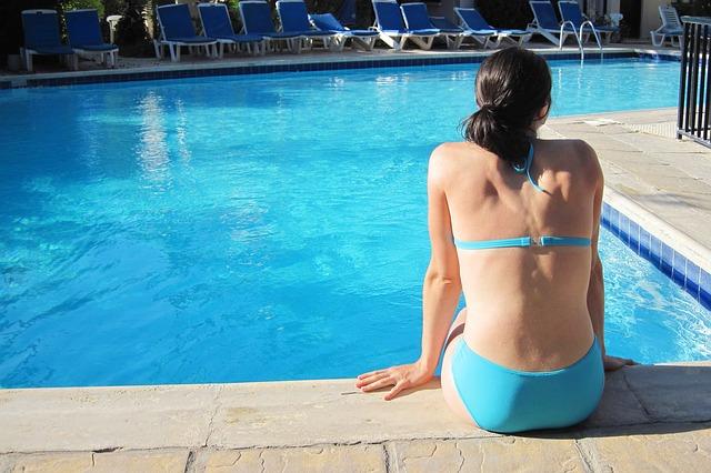 žena v bikinách a bazén